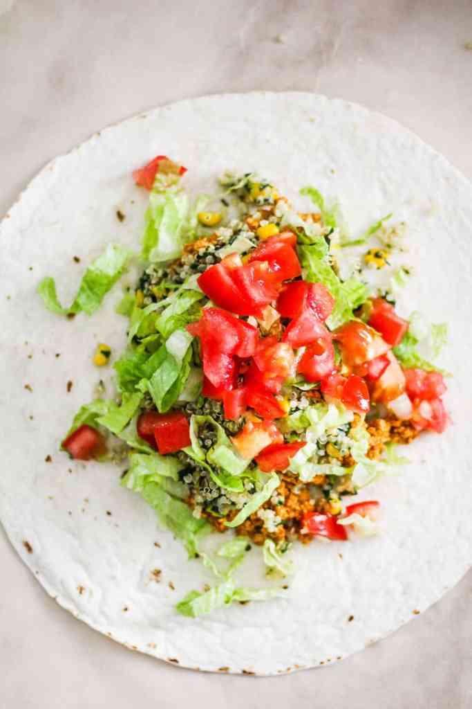 Open tortilla with burrito filling, lettuce, and tomato.