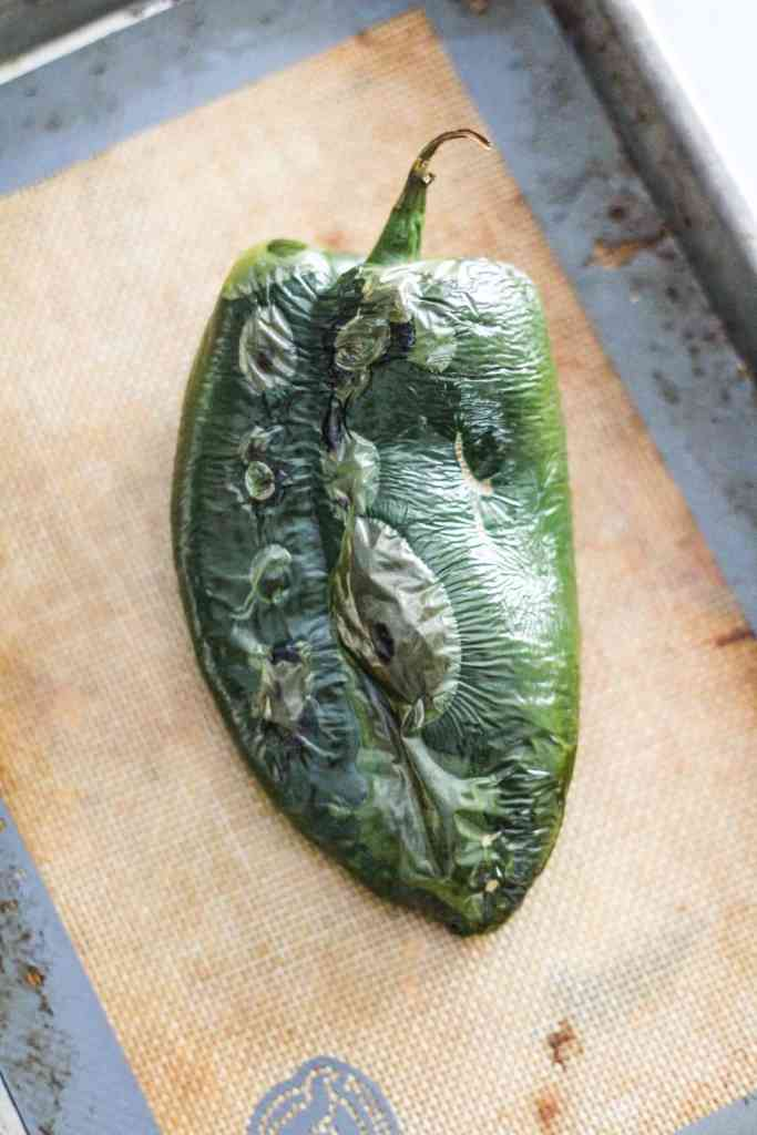 Roasted poblano pepper on a baking sheet.