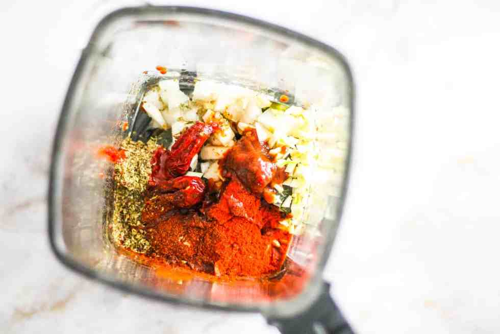 Ingredients for Sofrito sauce in a blender: spices, onion, and chipotle peppers in adobo sauce.