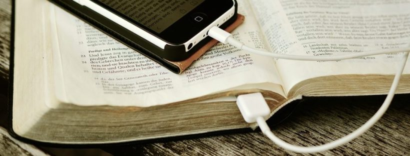 iPhone plugged into an Open Book