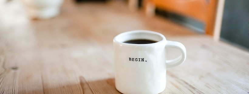 A white mug with the word 'begin' written in black letters.
