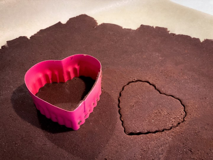 chocolate dough with heart chaped cookie cutter