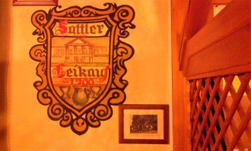 The coat of arms of the Buschenschank Sattler next tot the entry