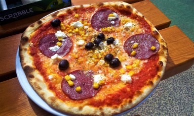 The pizza with feta, corn, salami and olives is very delicious