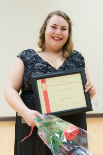 Grace VanHoven holds a bouquet and a plaque.