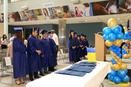 A group of Adult Education graduates, in caps and gowns, stand in Tassell M-TEC before a podium and a table with certificates on it.
