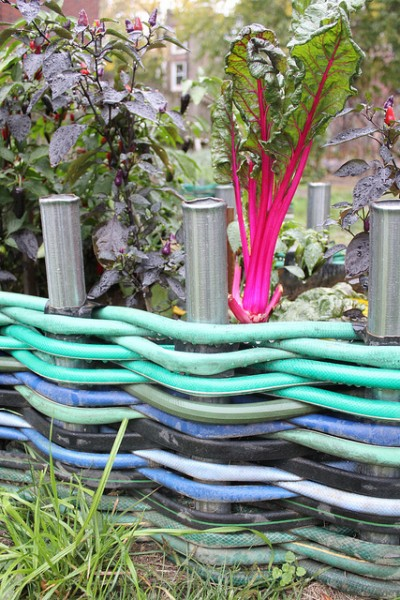 Weave Colorful Water Hoses Around Metal Poles That Are Dug Into The Ground For An Unique Way To Edge Your Garden Beds