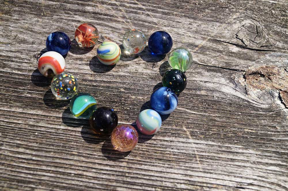 An assortment of glass marbles arranged in a heart shape on a piece of rough wood.