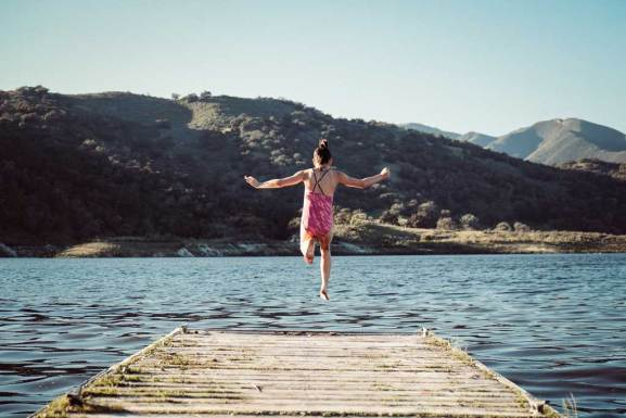 Summer overnight camp fun, girl jumping into a lake