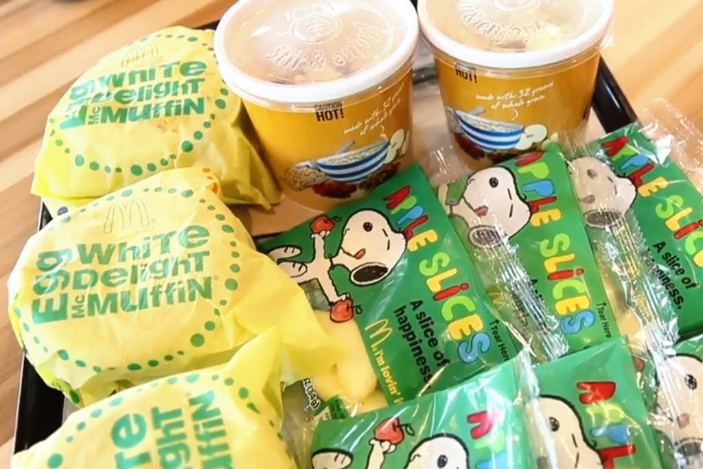 McDonald's Breakfast options on a dark tray. Three Egg White Delight McMuffins, two Fruite and Maple Oatmeal cups, and several packages of apple slices with Snoopy on the packaging.