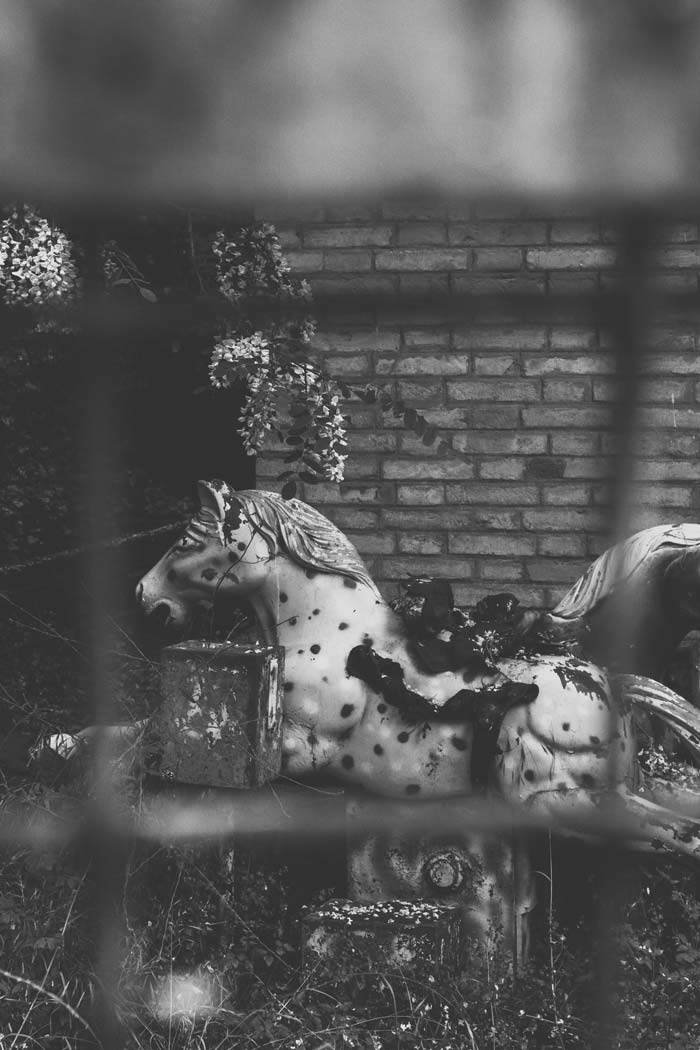 blacka nd white photo of carousel horse behind chain link fence