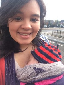 Lauren the doula smiling and wearing her newborn baby in a woven wrap