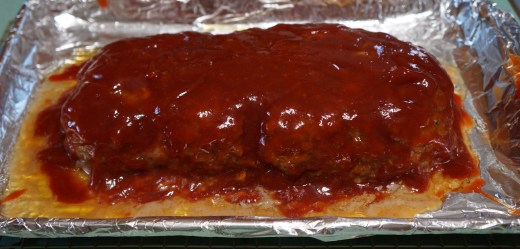 Glazed meatloaf going back into the oven to finish cooking.