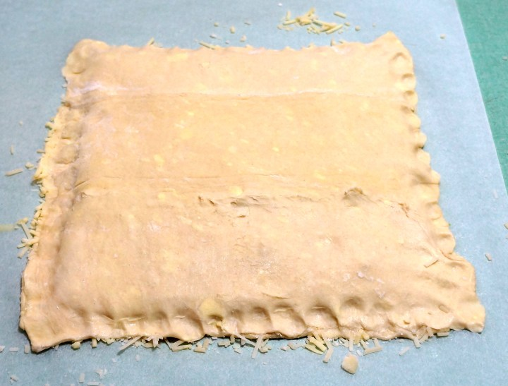 Place the other puff-pastry sheet on top of the cheese with the butter side facing down.  Crimp the edges using your fingers.