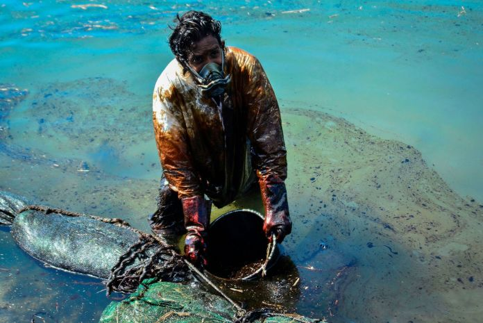 Man scoops leaked oil near Mauritius