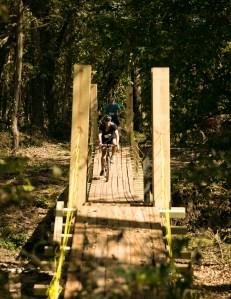 A cyclist crosses the suspension bridge