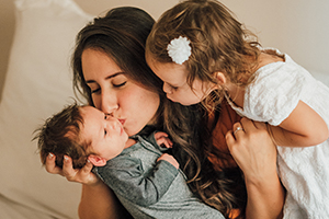 mother kissing baby with child