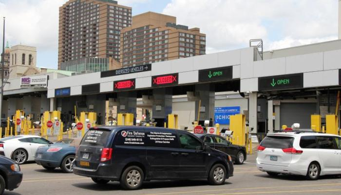 CBP checkpoint at the Detroit-Windsor Tunnel border crossing, with vehicles in the foreground.