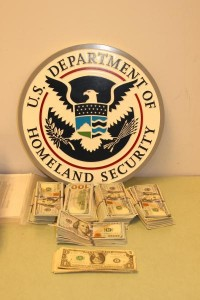Stacks of Money Seized at Houston Airport in front of a Homeland Security Seal