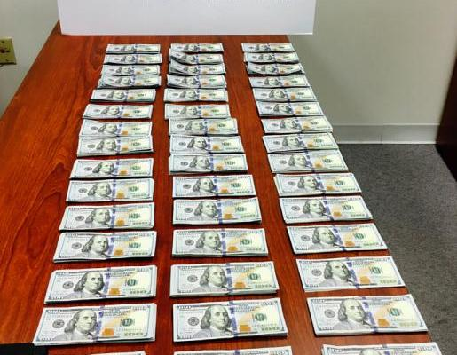 $45,000 of cash seized in envelopes by CBP laid out in 3 rows of 15 on on a wood table with a CBP logo