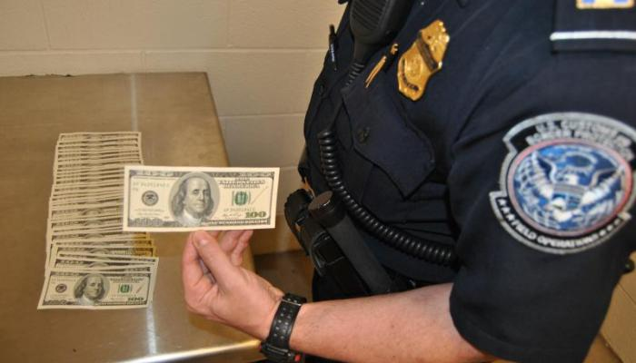 $3,700 in counterfeit cash seized by CBP from an Argentinian woman laid out on a metal table presented by a CBP officer