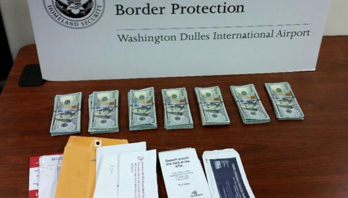 Stacks of cash and a pile of envelopes seized by U.S. Customs & Border Protection