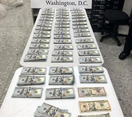 $98,762 in U.S. dollars seized by CBP stacked in front of a Dulles airport Washington DC sign