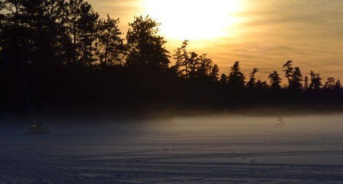 Snowmobiles driving on the ice on Lake Temagami in the winter as the sun sets.