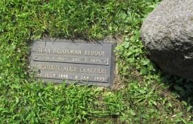 Grave marker set beside family stone
