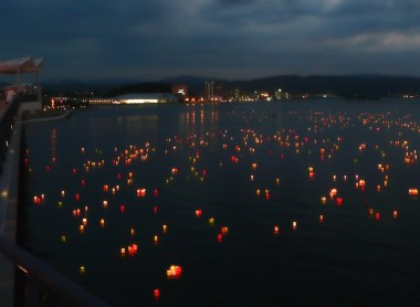 Picture of Obon laterns floating in a Japanese waterway.