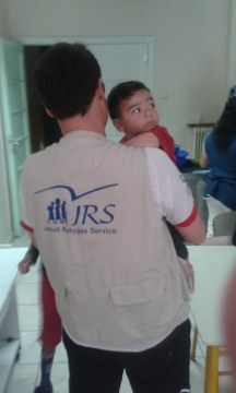 A volunteer with Jesuit Refugee Services with a refugee child