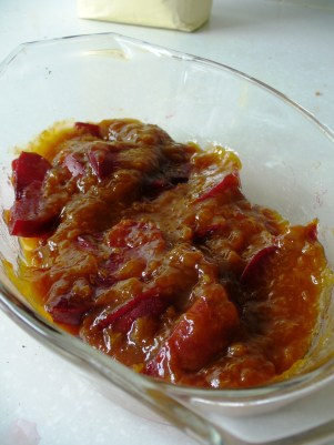 Plums smothered in apricot jam line the dish