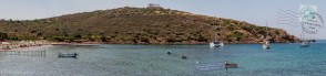 Bathers enjoy Sounion beach with the Temple of Poseidon on the hill above