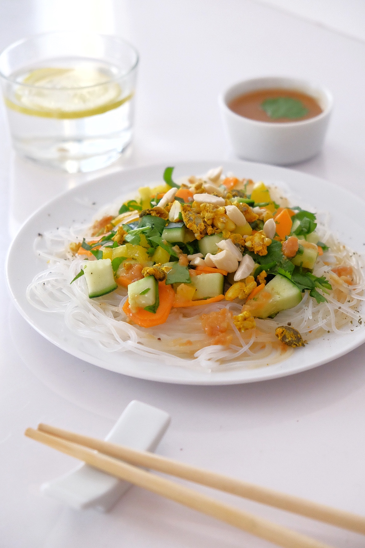 Ensalada de fideos de arroz con verduras crudas y salsa de cacahuetes