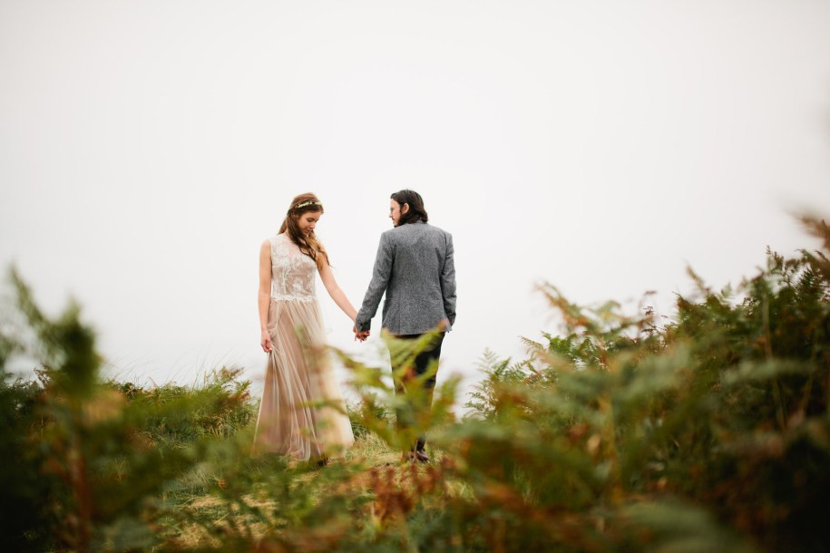 Boho style bride and groom by the English coast in Wales