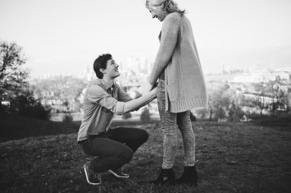 Man on his knees proposing to his girlfriend by London wedding photographer