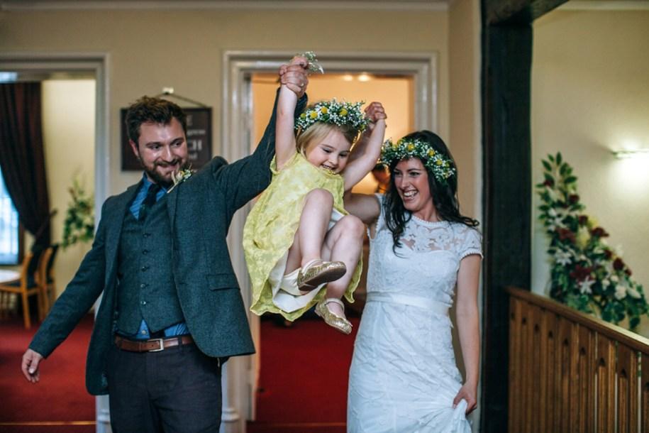 bride and groom swinging their daughter in HAWARDEN