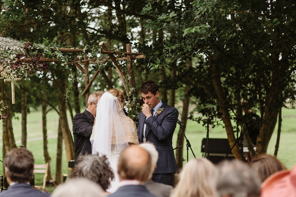 groom crying at outdoor wedding ceremony
