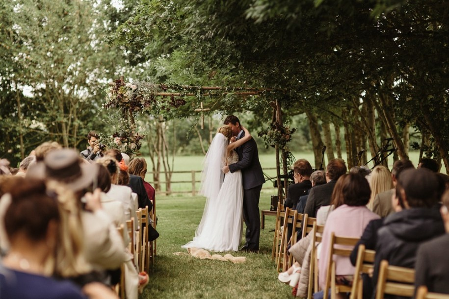 bride and groom kiss at garden wedding ceremony