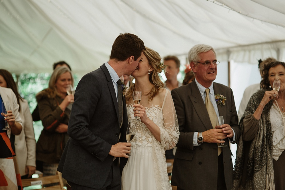 bride and groom kiss at marquee wedding during speeches