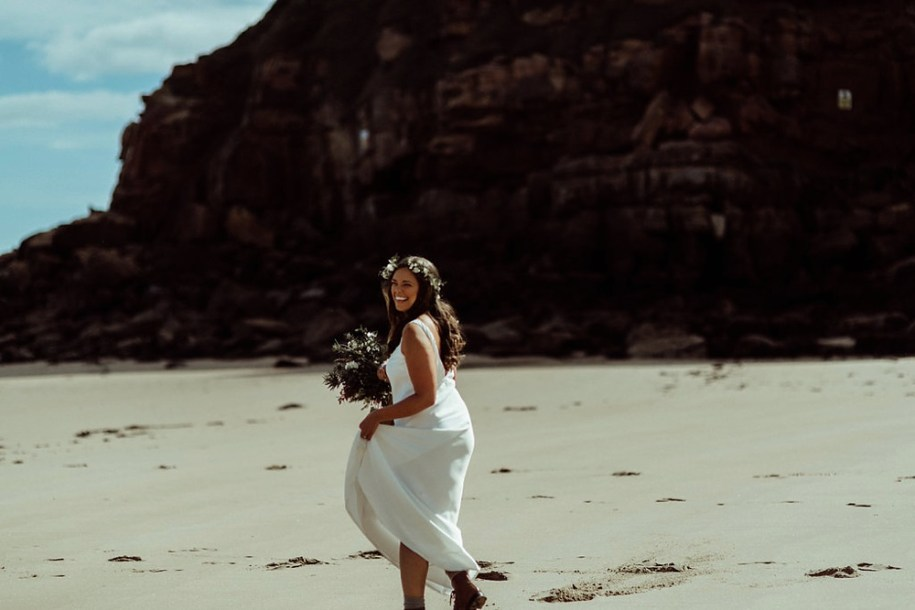 bride walking on the beach towards her groom