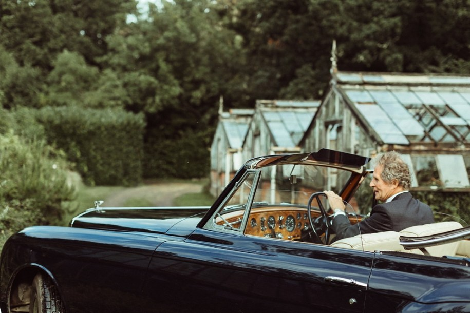 father of the bride in his vintage car after the wedding ceremony in New forest