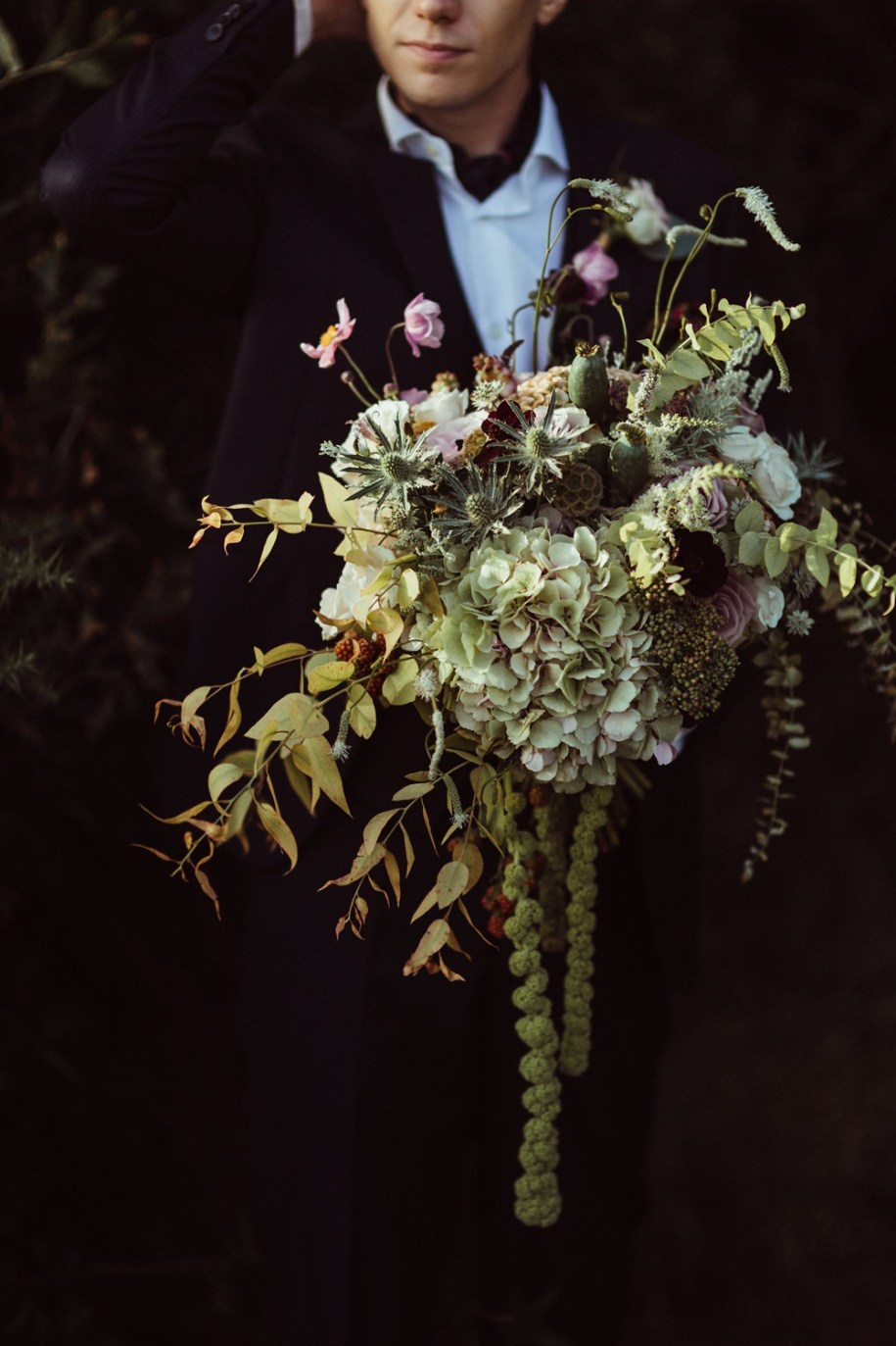groom holding a beautiful bouquet in New Forest during portrait shoot
