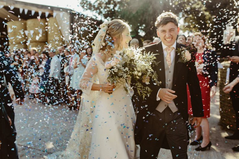 bride and groom after their barn wedding ceremony, walking for the confetti wedding pictures in sunshine