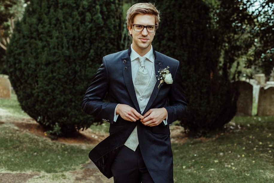 groom waiting in church courtyard for bride