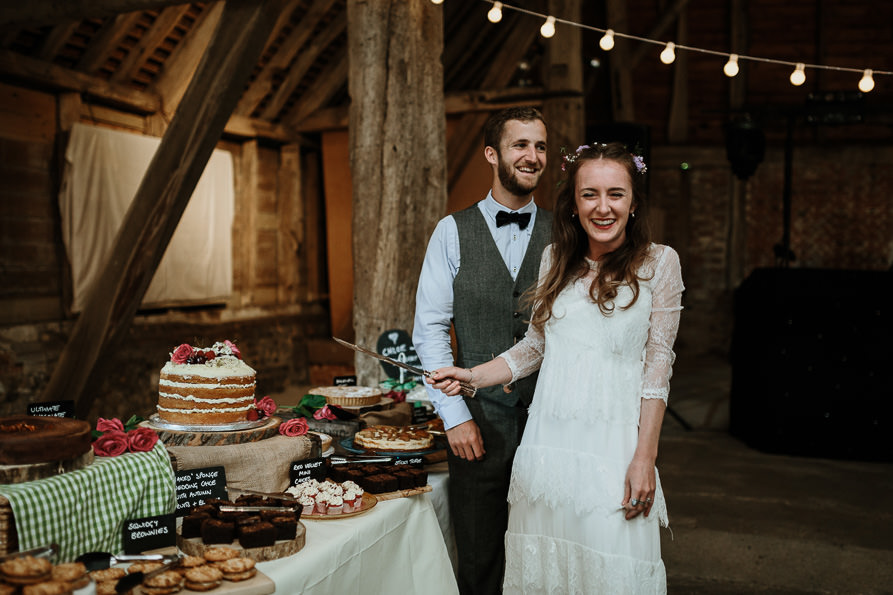 cake cutting during Wanborough Great Barn Wedding