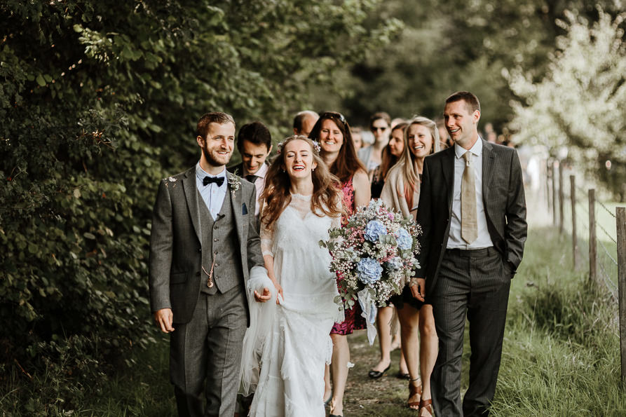 guests walking through forest after the outdoor wedding ceremony