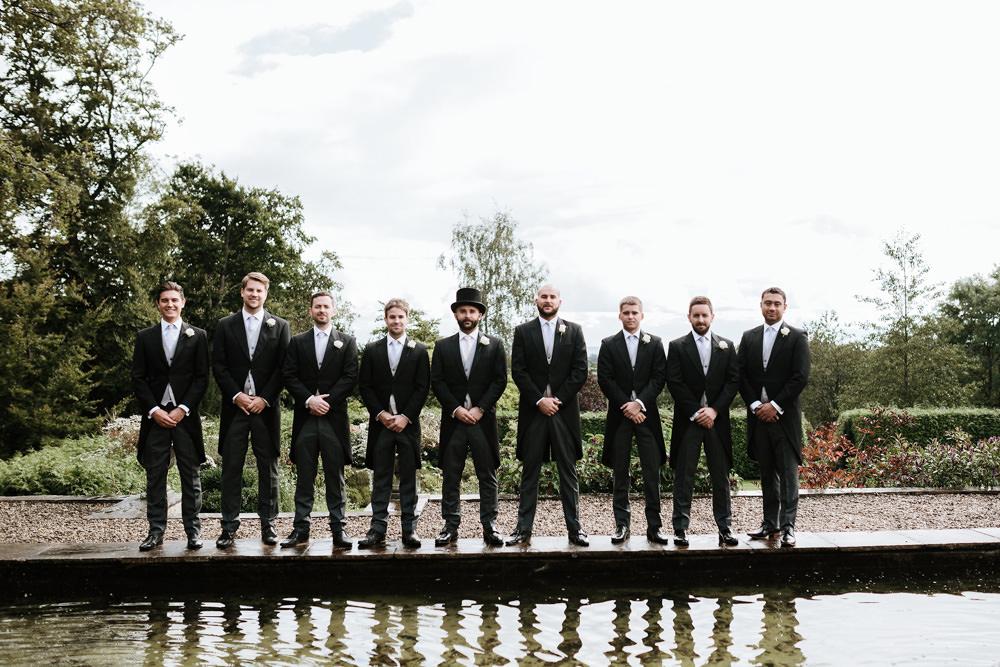 groomsmen in tuxedos by pool in dorset