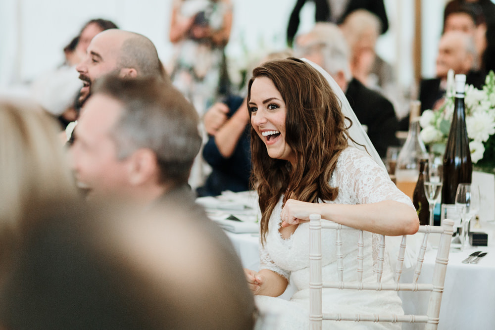 bride laughing during funny speeches in Dorset