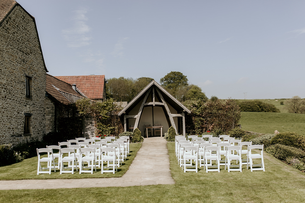 white chairs on the grass for an outdoor ceremony at The Kingscote Barn Wedding venue